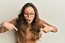 Young Hispanic Girl Wearing Casual Clothes And Glasses Pointing Down With Fingers Showing Advertisement, Surprised Face And Open Mouth