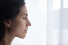 Close Up Profile Face View Of Hispanic Sad Woman Standing Indoor, Looks Out Window, Deeply In Mournful Thoughts Feels Depressed Experiencing Life Troubles. Cheerless Female Portrait, Problems Concept