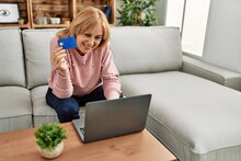 Middle Age Blonde Woman Buying Using Laptop And Credit Card Sitting On The Sofa At Home.