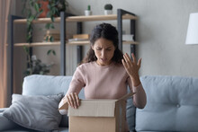 Angry Latin Woman Sit On Sofa Unpacking Parcel Feels Dissatisfied While Looks Inside Of Cardboard Box, Wrong Or Damaged Shopping Order, Bad Delivery Service, Client Displeased By Post Shipping Concept