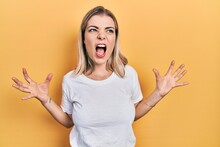 Beautiful Caucasian Woman Wearing Casual White T Shirt Crazy And Mad Shouting And Yelling With Aggressive Expression And Arms Raised. Frustration Concept.