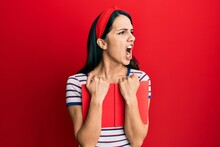 Young Hispanic Woman Holding Book Angry And Mad Screaming Frustrated And Furious, Shouting With Anger. Rage And Aggressive Concept.