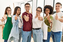 Group Of Young Draw Students Smiling Happy Doing Ok Sign With Thumbs Up Standing At Art Studio.