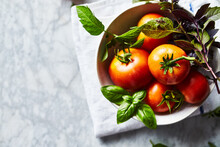 Freshly Picked Organic Tomatoes With Basil Leaves In A Bowl
