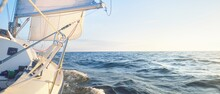 Sailing In The Cockpit Of A Yacht In An Open Sea At Sunrise. Clear Blue Sky, Warm Sunlight. Waves And Water Splashes. Sport And Recreation Theme