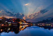 Beautiful Sunsets View Of Ban Rak Thai, Mae Hong Son, Thailand. The Dusk Scene After Sunset With The Reflection Of The Buildings And Night Market On The Pond.