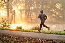 Male Runner Exercising At Autumn In Park