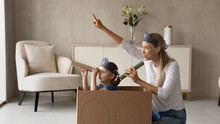 Excited Kid And Happy Mom Playing Pirates At Home, Sailing Toy Carton Box Ship, Looking Forward Through Spyglasses. Mother And Daughter Girl Enjoying Role Game, Home Activity, Entertainment, Amusement
