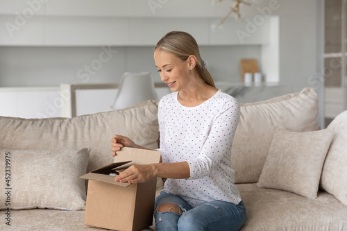 Obraz na plátně Happy woman unpacking container at home, opening carton box, looking inside package, sitting on couch