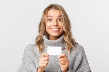 Close-up Of Excited Smiling Woman With Blond Hair, Holding Credit Card For Shopping, Standing Over White Background