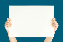 Women Hand Holding White Blank Paper Isolated On Blue Background With Clipping Path