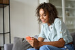 Smiling happy young African American woman holding cell phone sitting on sofa at home, using online mobile apps technology doing online shopping, dating in application, checking social media, texting.