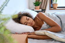 Young Calm African American Woman Model Sleeping Well With Eyes Closed Lying In Comfortable Bed On Orthopedic Mattress Lying On Soft Pillow At Home Having Healthy Night Sleep Relaxing In The Morning.