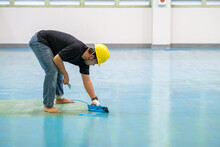 Construction Worker Using Trowel Spreading Epoxy Putty For Self-leveling Method Of Epoxy Floor Finishing Work