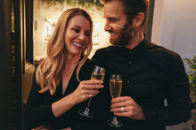 Cheerful Couple Toasting With Champagne Glasses