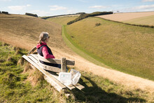 A Woman On A Bench Overlooking Horse Dale Near Fridaythorpe In The Yorkshire Wolds, UK.