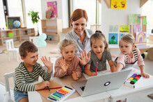 Group Of Small Nursery School Children With Teacher Indoors In Classroom, Using Laptop.