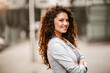Caucasian businesswoman with curly hair posing outside