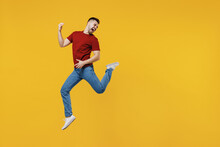Full Length Overjoyed Expressive Fun Happy Young Man Wear Red T-shirt Casual Clothes Jump High Playing Guitar Isolated On Plain Yellow Color Wall Background Studio Portrait. People Lifestyle Concept.