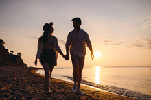 Full Body Lower Silhouette Young Couple Two Friends Family Man Woman In Casual Clothes Hold Hand Look To Each Other Walk Together At Sunrise Over Sea Beach Ocean Outdoor Seaside In Summer Day Evening.
