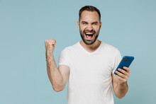 Young Overjoyed Happy Man Wear Casual Basic Blank Print Design White T-shirt Using Mobile Cell Phone Do Winner Gesture Clench Fist Isolated On Plain Pastel Light Blue Color Background Studio Portrait
