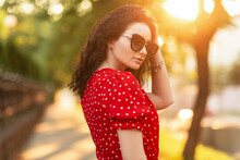 Beautiful Elegant Italian Girl In Fashionable Summer Bright Clothes With Glasses And A Retro Red Dress Walks In The City At Sunset