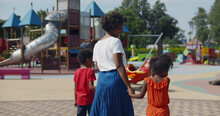Rear View Of African Woman With Two Kids Walking To Outdoors Playground