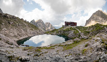 Valley With A Small Lake In The Middle, Located Between Sharp And Stony Mountain Range Of Lienz Dolomites (Karlsbader Hutte) Austria. The Slopes Are Barren, With Little Grass On It. Dangerous Mountai