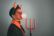 Profile Portrait Of A Girl Wearing A Devil Costume While Bubbling Gum
