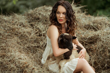 Brunette Caucasian Woman Sitting On The Hay Grass Holding A Baby Goat Wearing A White Dress