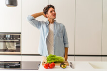 Young Mixed Race Man Preparing A Salad For Lunch Touching Back Of Head, Thinking And Making A Choice.