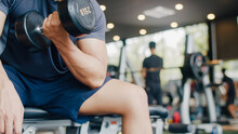 Young Athlete Asian Guy Exercising Doing Lifting Dumbbell Fat Burning Workout In Fitness Class. Sportsman Recreational Activity, Functional Training, People Working Out, Healthy Lifestyle Concept.