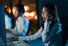 Millennial Asia Young Call Center Team Or Customer Support Service Executive Using Computer And Microphone Headset Working Technical Support In Late Night Office. Telemarketing Or Sales Job Concept.