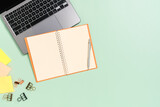 Fototapeta Kawa jest smaczna - Creative flat lay photo of workspace desk. Top view office desk with laptop, coffee cup and open mockup black notebook on pastel green color background. Top view mock up with copy space photography.
