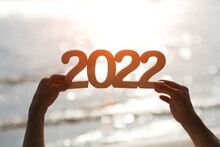 Hands Hold Wooden Numbers 2022 Against The Background Of Water At Sunset. Climate Change. Ecology.  Happy New Year Concept
