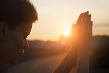 Hands Of Young Christian Woman Praying At Sunrise Light, Religion And Spirituality Concept