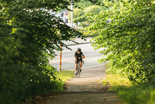 Smiling Hispanic Cyclist Riding Bike On Path In Park