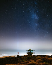 Person On Beach Under Starry Sky With Milky Way At Night