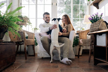 Couple Embracing Fox Terrier In Armchair At Home