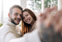 Smiling Couple Taking Selfie In House Room