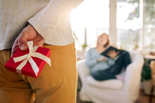 Crop Man With Gift Box Against Girlfriend In Armchair