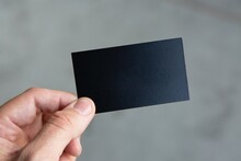 Hand Holding Empty Black Piece Of Paper For Advertisement