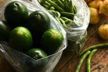 A Top View Image Of Organically Grown Potatoes, Beans, And Cucumbers On A Rustic Table.