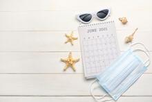 Calendar, Sunglasses, Seashells And Medical Masks On Light Wooden Background