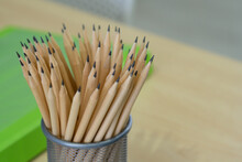 Many Pencils Are In The Mesh Box On A Wooden Table. Space For Text. Close-up Photo