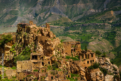 Ruins of the ancient village of Gamsutl with abandoned stone walls of a building on top of a mountain peak against the background of mountains in summer in Dagestan, Russia