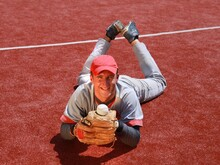 Baseball Player Lying On Field With Ball