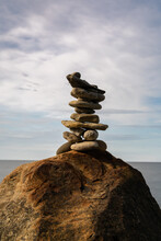 Meditative Rock Cairn On Top Of A Boulder With Long Exposure Ocean And Sky In The Background