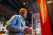 Smiling African-American Man In Warm Denim Jacket With Wireless Earphones Uses Self-service Kiosk To Order Snack In Cafe