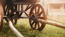 An Old Wooden Cart With Large Wheels Stands In A Meadow With Blooming Yellow Flowers, Near Rural Wooden Houses. The Village And Vintage Transport.